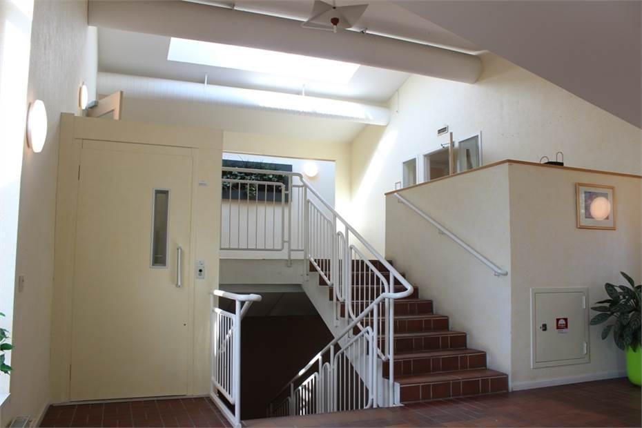 Hall med trappa och hiss upp till lokalen.