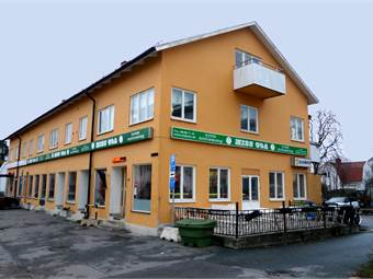 Husfsaden från framsidan med en entré till lokalen intill restaurangen